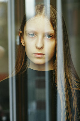 Portrait of a sad teenage girl through a window - p1540m2100972 by Marie Tercafs