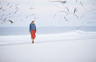 Woman walking next to the ocean surrounded by flying seagulls - p1577m2150314 by zhenikeyev