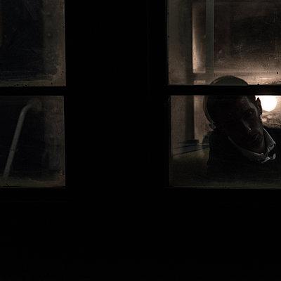 Man sleeping by the window, night shot - p1624m2223734 by Gabriela Torres Ruiz