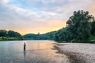 Germany, Upper Bavaria, Burghausen, Salzach valley, fly fisherman at sunset - p300m2023552 by Hans Mitterer