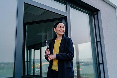 Smiling businesswoman looking away while holding laptop at doorframe - p300m2276988 by Oxana Guryanova