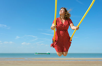 Woman on a swing on a beach, Zoutelande, Zeeland, Netherlands, Europe - p429m1513648 by Mischa Keijser