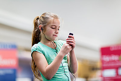 Caucasian girl listening to mp3 player - p555m1413783 by Marc Romanelli