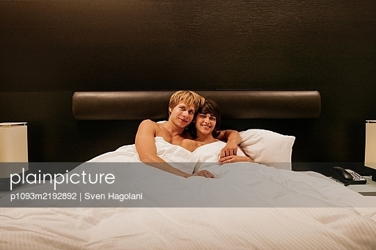 Young couple in hotel bed, portrait - p1093m2192892 by Sven Hagolani