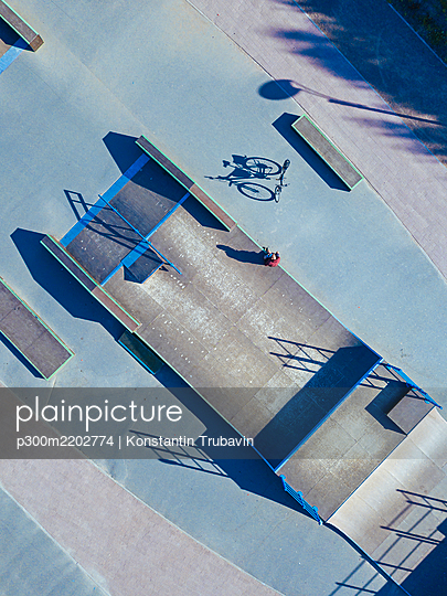 Man sitting on concrete ramp in skate park, aerial view - p300m2202774 by Konstantin Trubavin