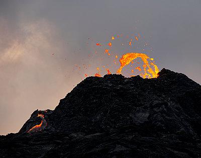 Orange lava over carter of erupting volcano at sunset - p1166m2268478 by Cavan Images