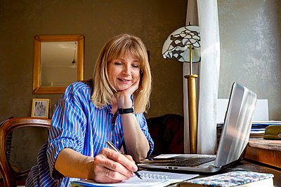 Mature woman writing on notepad while sitting with laptop at home - p300m2282008 by Irina Heß