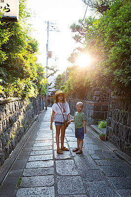 Siblings on cobbled footpath in Kyoto - p756m2122763 by Bénédicte Lassalle