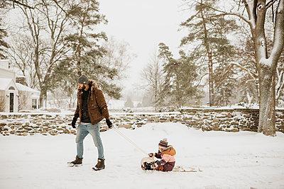 Canada, Ontario, Father pulling daughter (2-3) on toboggan - p924m2271213 by Sara Monika