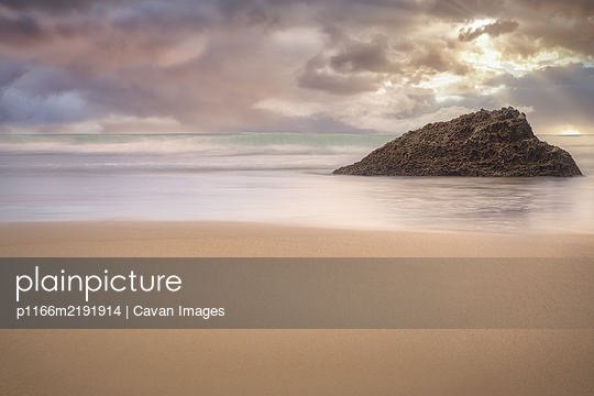 A rock formation isolated in the beach at sunset - p1166m2191914 by Cavan Images