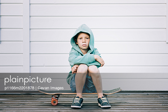 young boy sat on a skateboard with a hoodie on looking grumpy - p1166m2201878 by Cavan Images
