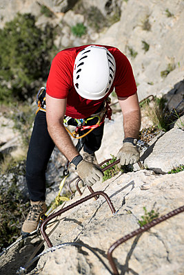 High angle view of male hiker climbing rock - p1166m1577407 by Cavan Social