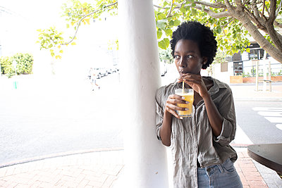 Young African woman has a soft drink - p1640m2260095 by Holly & John