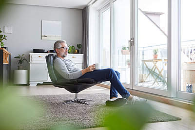 Mature man sitting on leather chair in his living room relaxing with cup of coffee - p300m2030415 von Rainer Berg