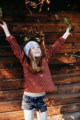 Smiling girl standing in front of a wooden wall with arms outstretched outdoors - p300m2144060 von Epiximages