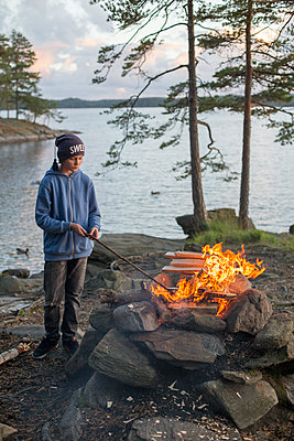 Sweden, Vastergotland, Lerum, Boy (12-13) making bonfire by lake Harsjon at sunset - p352m1100585f by Andreas Ulvdell