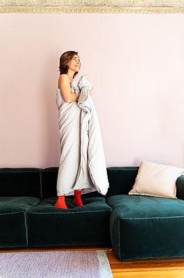 Frau hält sich Bettdecke am Körper - p432m2168903 von mia takahara