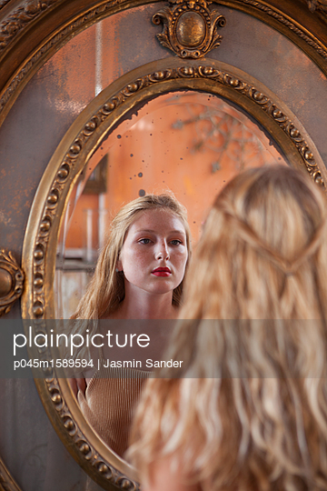 Frau sieht sich selbst im Spiegeln an - p045m1589594 von Jasmin Sander
