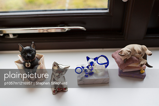Verschiedene Katzenfigürchen auf einem Fensterbrett - p1057m1216957 von Stephen Shepherd