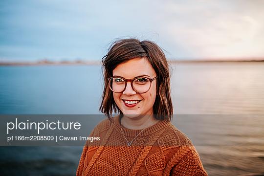 Center Portrait of a woman wearing glasses near a lake - p1166m2208509 by Cavan Images