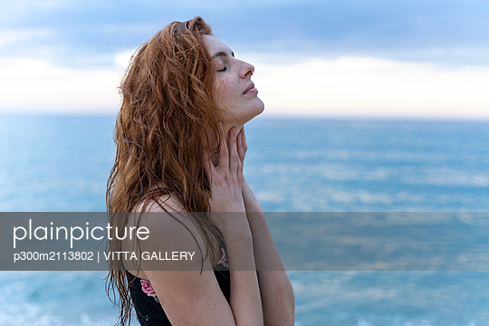 Young man with eyes closed in front of the sea - p300m2113802 von VITTA GALLERY