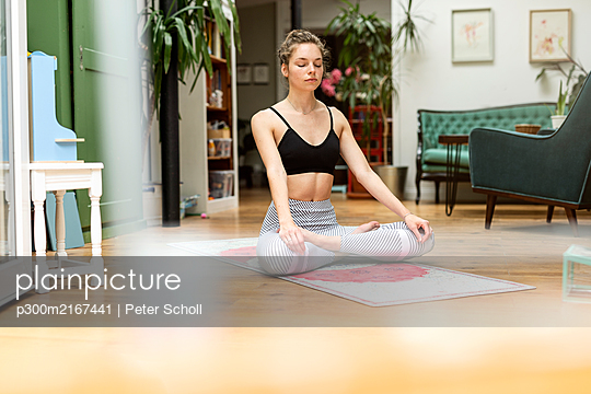 Young woman practicing yoga at home - p300m2167441 by Peter Scholl
