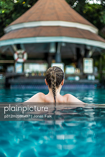 Young woman relaxing in swimming pool - p312m2086497 by Jonas Falk