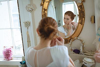 Young bride in wedding dress wearing earrings - p1315m1578906 by Wavebreak