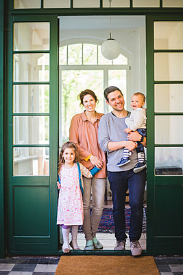 Full length portrait of smiling family standing at home entrance - p426m2127330 by Maskot