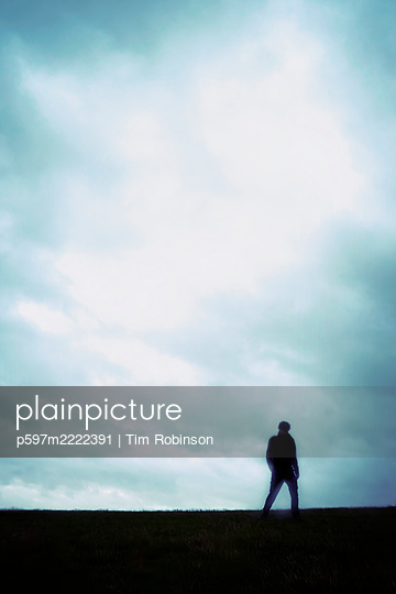 Blurred man walking on grass field - p597m2222391 by Tim Robinson