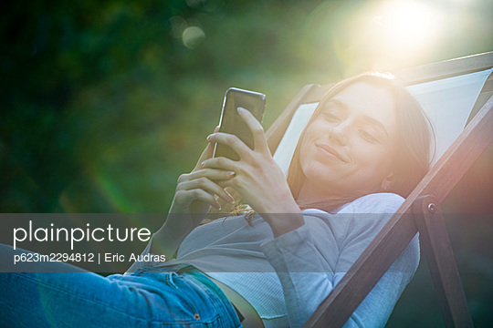 Young woman using smartphone in park - p623m2294812 by Eric Audras