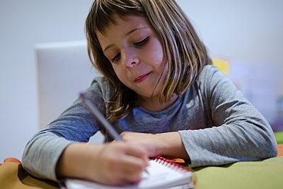 blonde girl doing her homework in the notebook - p1166m2179582 by Cavan Images
