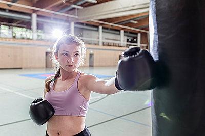 Female boxer practising at punchbag in sports hall - p300m2144497 von Stefanie Baum
