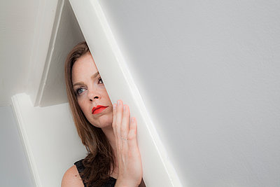 Young woman looking out her doorway. - p397m1169678 by Peter Glass