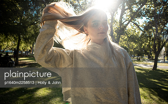 Teenage girl with blond hair in a park - p1640m2258513 by Holly & John