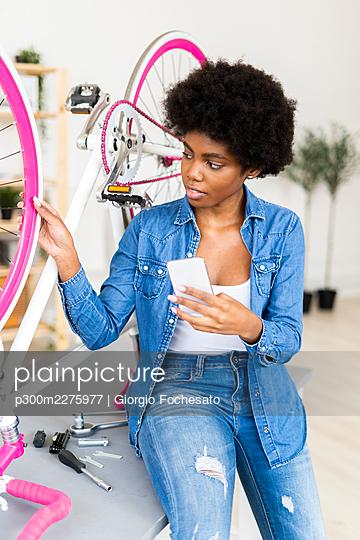 Woman repairs bike holding phone - p300m2275977 von Giorgio Fochesato