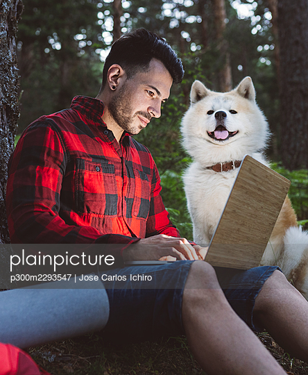 Man working through laptop while sitting by pet at forest - p300m2293547 by Jose Carlos Ichiro
