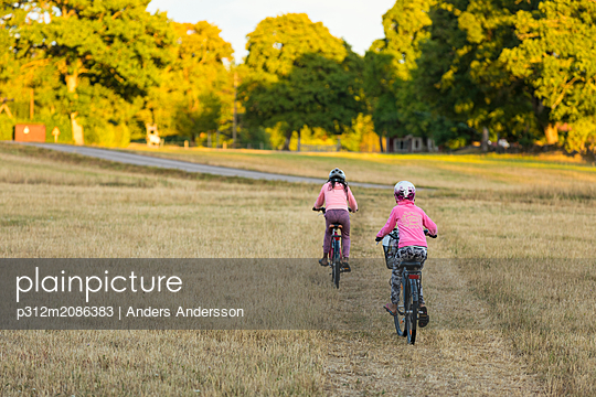 Girls on bicycles in meadow - p312m2086383 by Anders Andersson