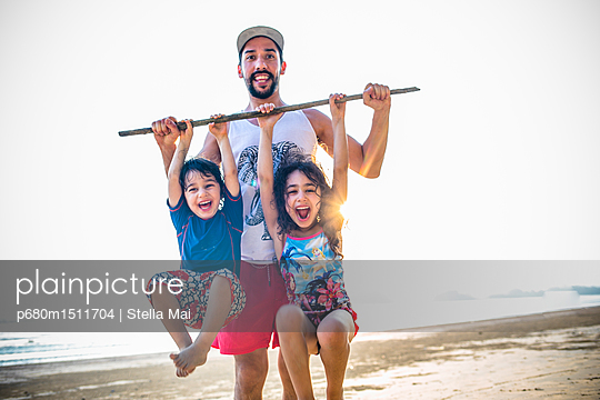 Father and children on beach, portrait - p680m1511704 by Stella Mai