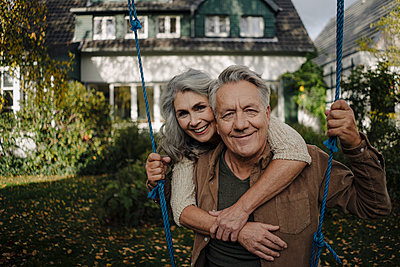 Portrait of a happy woman embracing senior man on a swing in garden - p300m2155004 by Gustafsson