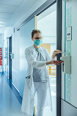 Doctor disinfecting her hands in hospital - p300m2180979 by Mareen Fischinger