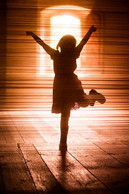 Silhouette of girl dancing on wooden floor - p312m1229099 by Peter Rutherhagen