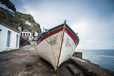 Fishing boat on the shore at the water's edge; Ponta do Arnel, Sao Miguel, Azores, Portugal - p442m1180094 by Dosfotos