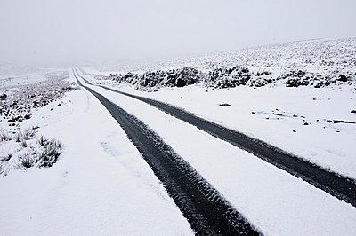 Car tyre tracks on a snowy road on the Mynydd Epynt moorland, Powys, Wales, United Kingdom, Europe - p871m1048015 by Graham Lawrence