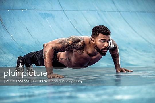 Tattooed physical athlete doing pushups on sports field - p300m1581331 von Daniel Waschnig Photography
