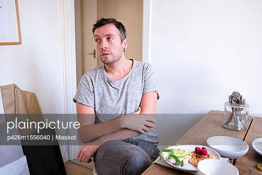 Man sitting by food on table at home - p426m1556040 by Maskot