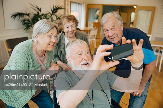 Disabled senior man taking selfie with friends at retirement home - p426m2149312 by Maskot