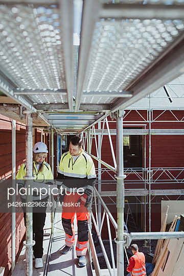 Full length of female building contractor discussing over floor plan with male colleague while walking at scaffolding - p426m2296270 by Maskot