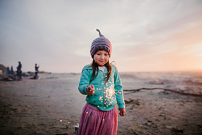 Girl wearing knit hat while holding illuminated sparkler against sky at beach - p1166m1534182 by Cavan Images