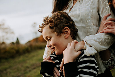 Close-up of smiling brother with mother and sister at park - p1166m1555655 by Cavan Images